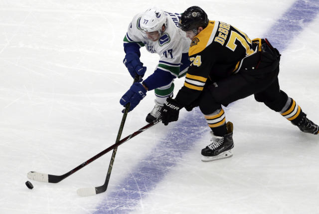 Vancouver Canucks right wing Nikolay Goldobin (77) and Boston Bruins left wing Jake DeBrusk (74) compete for the puck during the first period of an NHL hockey game Thursday, Nov. 8, 2018, in Boston. (AP Photo/Elise Amendola)