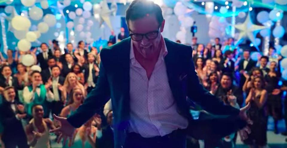 Matthew Lillard dances on a stage in front of a group of students at prom