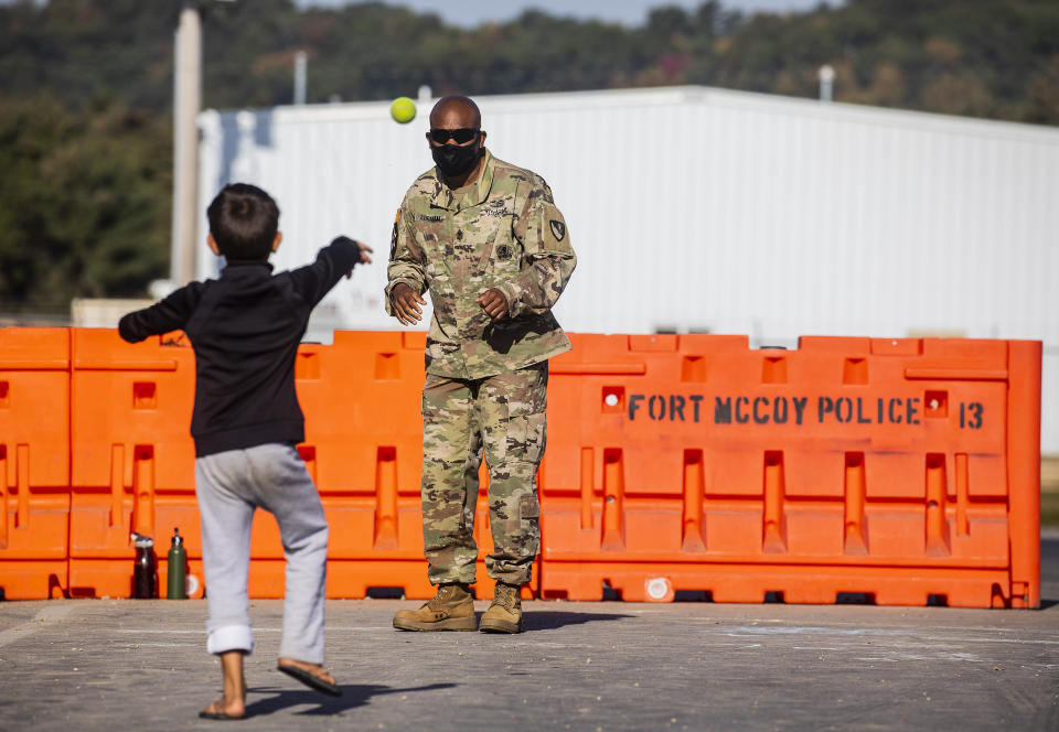 First Sgt. Abraham plays catch with an Afghan refugee child in the Village where Afghans are living temporarily at the Ft. McCoy U.S. Army base on Thursday, Sept. 30, 2021 in Ft. McCoy, Wis. The fort is one of eight military installations across the country that are temporarily housing the tens of thousands of Afghans who were forced to flee their homeland in August after the U.S. withdrew its forces from Afghanistan and the Taliban took control. (Barbara Davidson/Pool Photo via AP)
