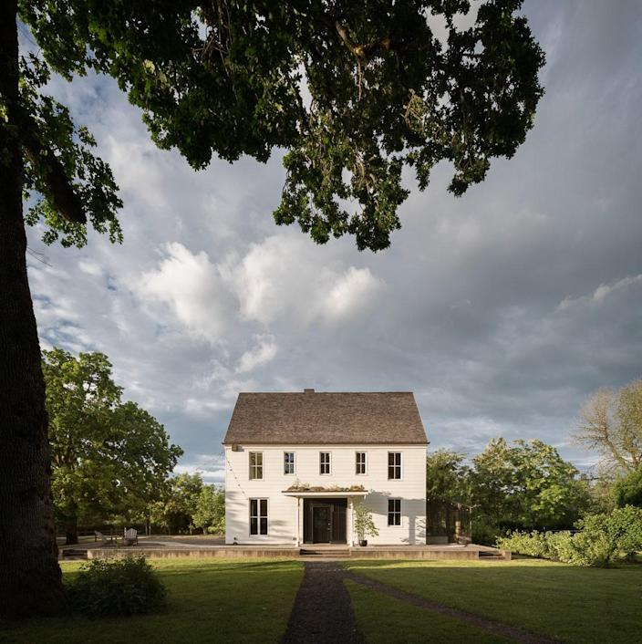 """Wild Goose Farmhouse, pictured from under an oak tree, is where interior designer Jessica Helgerson and architect Yianni Doulis live with their two children, Max and Penelope. """"When we were designing the house, we decided to give it a spirit, to help guide design decisions,"""" Helgerson says. """"We created a character—a slightly forbidding spinster aunt, tall, thin, always dressed in starched linen dresses with high collars. She dies, and as you are going through her things, you discover a drawer full of fabulously beautiful lingerie and a bundle of letters from a Moroccan lover. She is the spirit of Wild Goose Farmhouse."""""""
