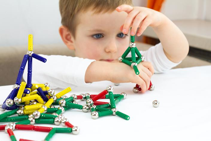 Cute child playing with lots of colorful magnet on white background