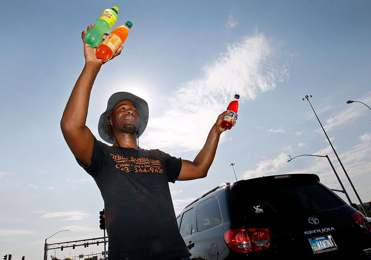 <p>Thirty-three year old Eric Maurice Clark sells cold bottled drinks to drivers at a busy intersection on June 20, 2017 in Phoenix, Arizona. Record temperatures of 118 to 120 degrees were expected on Tuesday for the Phoenix-metro area. (Ralph Freso/Getty Images) </p>
