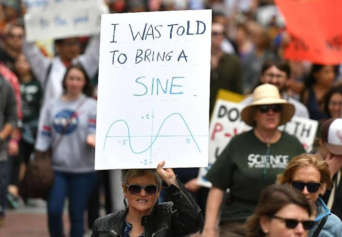 People holds up signs during the March for Science in San Francisco, California on April 22, 2017 (AFP Photo/Josh Edelson)