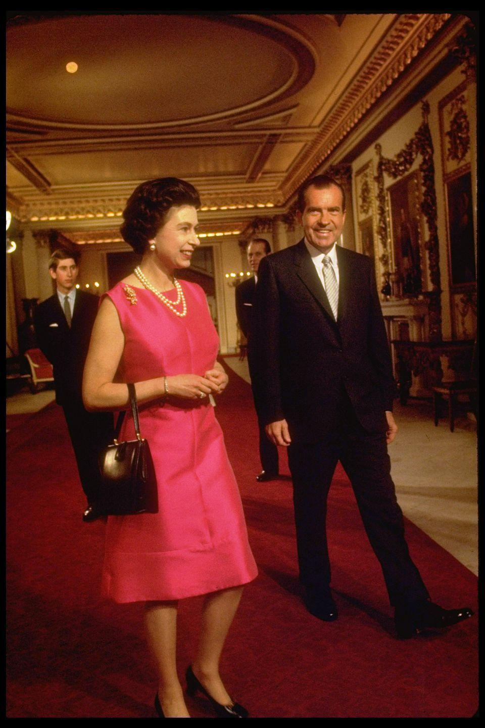 <p>The Queen and Nixon walking through the corridors of Buckingham Palace. In the background you can see a young Prince Charles. </p>
