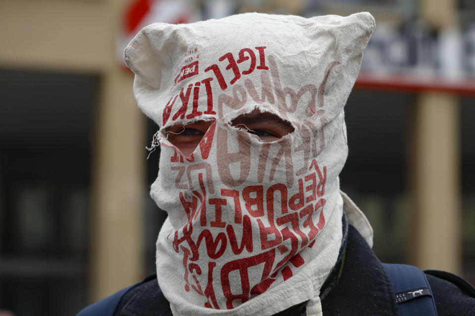 A man wears a bag over his head instead of a mask as demonstrators gather to protest the COVID-19 preventive measures downtown Prague, Czech Republic, Wednesday, Oct. 28, 2020. Coronavirus infections in the Czech Republic have again jumped to record levels amid new restrictive measures imposed by the government to curb the spread. (AP Photo/Petr David Josek)
