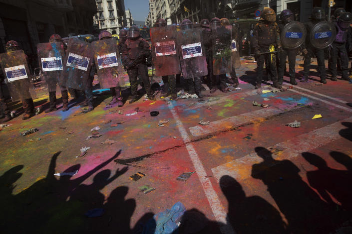 Catalan police officers cordon off the street to stop pro independence demonstrators on their way to meet demonstrations by members and supporters of National Police and Guardia Civil, as coloured powder is seen on the ground after being thrown by protesters, in Barcelona on Saturday, Sept. 29, 2018. (AP Photo/Emilio Morenatti)
