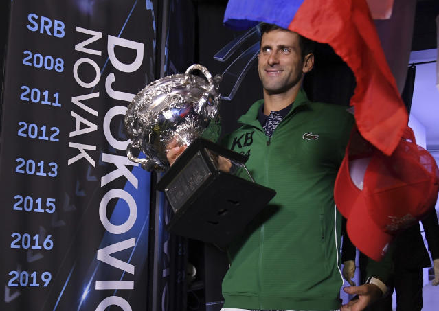 Serbia's Novak Djokovic carries the Norman Brookes Challenge Cup onto Margaret Court Arena to celebrate with fans after defeating Austria's Dominic Thiem in the men's singles final of the Australian Open tennis championship in Melbourne, Australia, early Monday, Feb. 3, 2020. (AP Photo/Andy Brownbill)