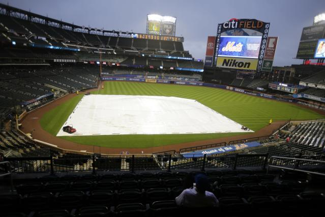 Fans wait during a rain delay for the start of the first game of a baseball doubleheader Wednesday, Sept. 12, 2018, in New York. (AP Photo/Frank Franklin II)