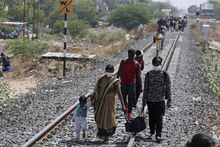 Migrant workers, desperate to return to their hometowns, walk along rail tracks towards a train station in Ahmedabad, India, on Monday, May 11, 2020. (AP Photo/Ajit Solanki)