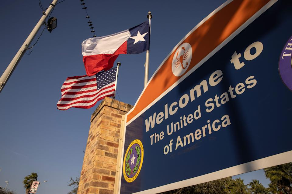 The U.S. and Texas flags fly near the U.S.-Mexico border on February 24, 2021 in Brownsville, Texas.
