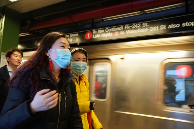 People wear surgical masks in the subway station at Times Square in New York