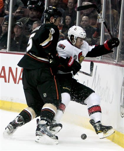 Ottawa Senators right wing Andre Petersson, right, from Sweden, is checked into the boards by Anaheim Ducks defenseman Luca Sbisa, from Italy, during the first period of an NHL hockey game on Saturday, Jan. 21, 2012, in Anaheim, Calif. (AP Photo/Bret Hartman)