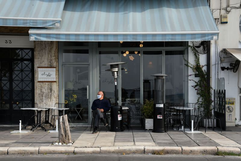 A man sits outside a closed cafe, amid the coronavirus disease (COVID-19) pandemic, in Thessaloniki