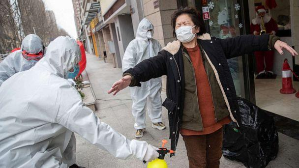 PHOTO: A woman who has recovered from the coronavirus is disinfected by volunteers as she arrives at a hotel for a 14-day quarantine after being discharged from a hospital in Wuhan, in China, March 1, 2020. (AFP/Getty Images)