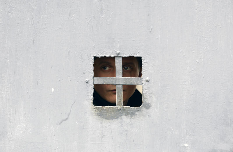 A Ukrainian soldier guarding a military base looks through a door at the Black Sea port of Sevastopol in Crimea, Ukraine, Saturday, March 8, 2014. A Ukrainian officer at the military base said that pro-Russia soldiers crashed a truck through its gates late on Friday in an attempt to take it over. (AP Photo/Darko Vojinovic)