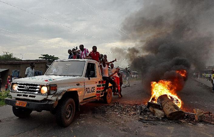 Protestors opposed to a third term for the Burundian President hitch a ride on a police vehicle past a burning barricade in the Cibitoke neighborhood of Bujumbura on May 19, 2015 (AFP Photo/Carl de Souza)