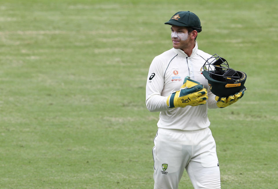 Australia's Tim Paine carries a helmet during play on day two of the fourth cricket test between India and Australia at the Gabba, Brisbane, Australia, Saturday, Jan. 16, 2021. (AP Photo/Tertius Pickard)
