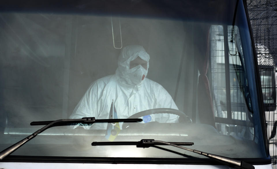 A masked driver is seen through a bus window carrying passengers from the Ukrainian aircraft chartered by the Ukrainian government for evacuation from the Chinese city of Wuhan, leave the the gate upon their landing at airport outside Kharkiv, Ukraine, Thursday, Feb. 20, 2020. Ukraine's effort to evacuate more than 70 people from China due to the outbreak of the new COVID-19 virus was delayed because of bad weather as evacuees travel to a hospital where they are expected to be quarantined. (AP Photo/Igor Chekachkov)