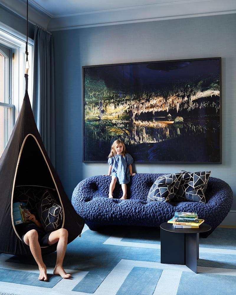 In a sitting area, a Victoria Sambunaris photograph hangs over a sofa by R. & E. Bouroullec for Ligne Roset.