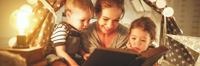 Mother and children reading a book.