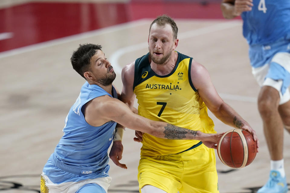 Argentina's Nicolas Laprovittola, left, tries to steal the ball from Australia's Joe Ingles (7) during a men's basketball quarterfinal round game at the 2020 Summer Olympics, Tuesday, Aug. 3, 2021, in Saitama, Japan. (AP Photo/Charlie Neibergall)