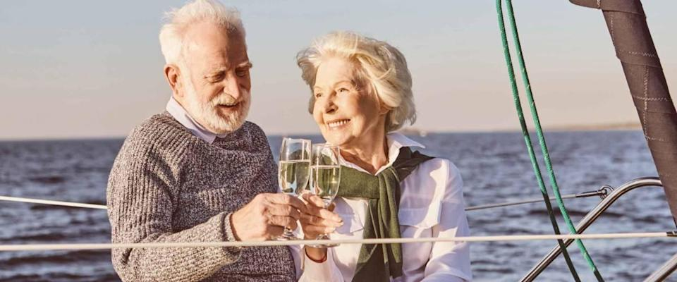 Cheers. Close up of happy senior couple sitting on the side of sail boat or yacht deck floating in sea. Man and woman drinking wine or champagne, enjoying the view