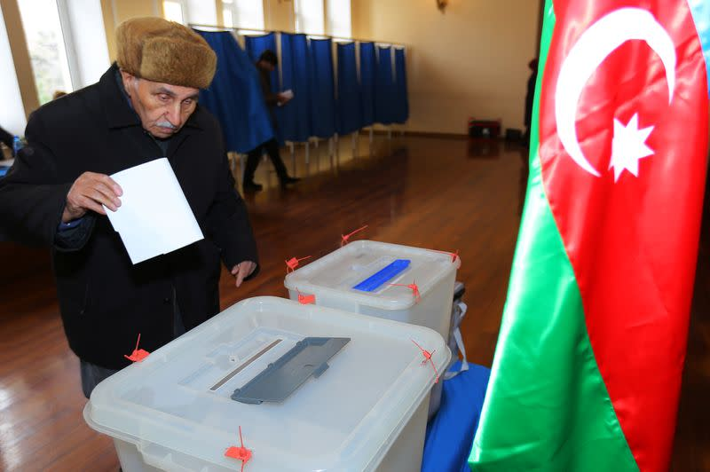 A man casts his vote at a polling station during a snap parliamentary election in Baku