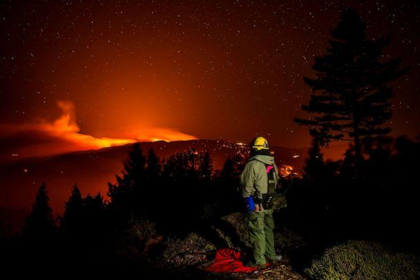 PHOTO: A man watches the Kincade fire burn on a ridge between Lake and Sonoma Counties, as he stands watch at a home above Knights Valley, east of Healdsburg, Calif., Oct. 29, 2019. (AFP via Getty Images, FILE)