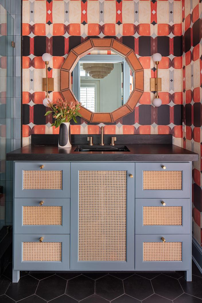 A warm orange Ford B wall covering by Lindsay is named for one of her sons and encompasses the boys' bathroom. Accent pattern is incorporated subtly through the black hexagonal Clé tile and the natural cane webbing on the custom blue vanity. The brass wall sconces are by Tech Lighting and the studded camel leather mirror is by Made Goods.