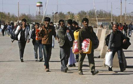 Group of Afghan migrant workers enter Afghan territory after leaving Iran at the Islam Qala border in Herat province