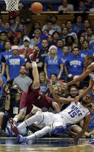 Duke's Josh Hairston (15) falls to the floor as Elon's Jack Isenbarger is upended while going for the ball during the first half of an NCAA college basketball game in Durham, N.C., Thursday, Dec. 20, 2012. (AP Photo/Gerry Broome)