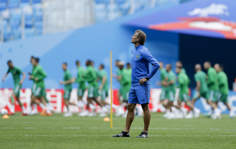 Morocco players run past their coach Herve Renard during the official training of Morocco on the eve of the group B match between Morocco and Iran at the 2018 soccer World Cup in the St. Petersburg Stadium in St. Petersburg, Russia, Thursday, June 14, 2018. (AP Photo/Andrew Medichini)