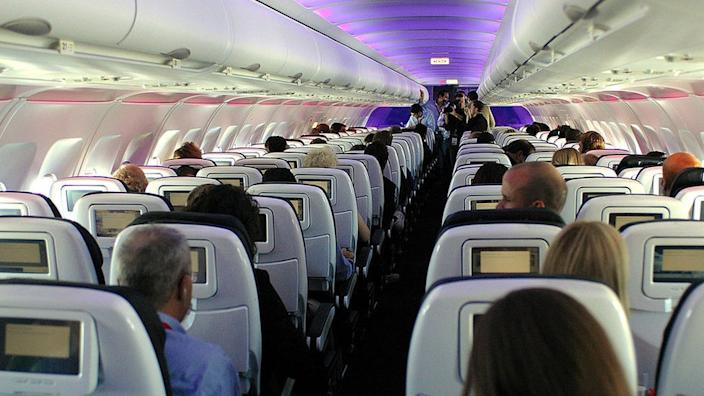 Passengers in custom-designed leather chairs enjoy Virgin America airlines mood-lit cabins and in-flight entertainment system