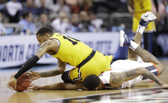 UMBC's Jairus Lyles (10) falls on top of Virginia's Isaiah Wilkins as they chase the ball during the first half of a first-round game in the NCAA men's college basketball tournament in Charlotte, N.C., Friday, March 16, 2018. (AP Photo/Gerry Broome)