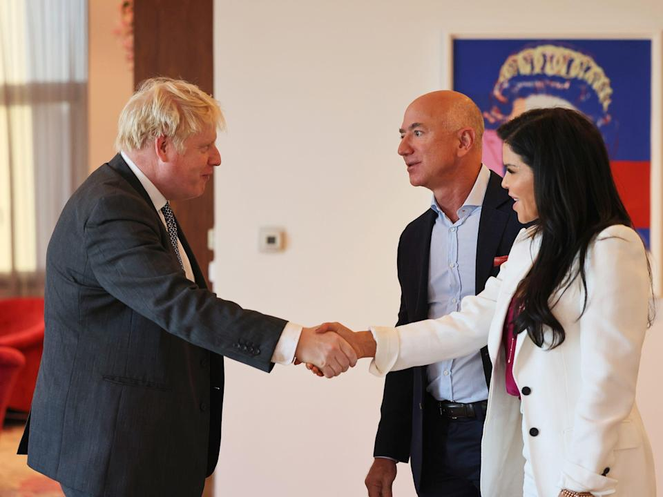 UK Prime Minister Boris Johnson (left) shakes hands with Jeff Bezos' girlfriend Lauren Sánchez while Jeff Bezos stands in the background.