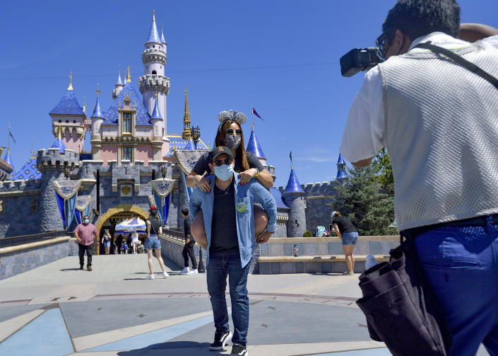 Anaheim, CA - April 30: Alexis Rangel holds his wife, Carla Rangel in front of Sleeping Beauty Castle at Disneyland as they pose for a picture in Anaheim, CA, on Friday, April 30, 2021. The resort