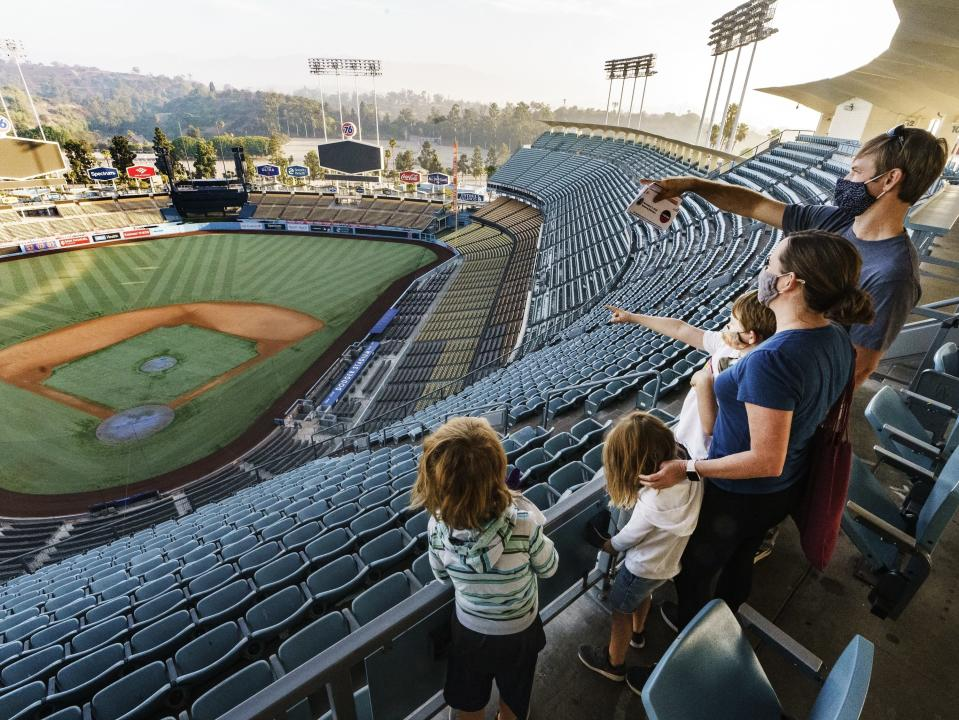Voters Brandon Malmberg and wife, Debbie explains the rules of baseball to their sons, Ashton, 7, Penn, 6, and Emmett 4, after voting in-person on Election Day at Dodger Stadium in Los Angeles, Tuesday, Nov. 3, 2020. (AP Photo/Damian Dovarganes)