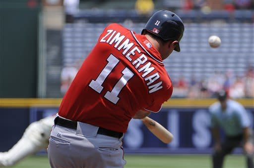 Washington Nationals' Ryan Zimmerman (11) hits a double against the Atlanta Braves, scoring Bryce Harper, in the first inning of their baseball game on Sunday, July 1, 2012, at Turner Field in Atlanta. (AP Photo/David Tulis)