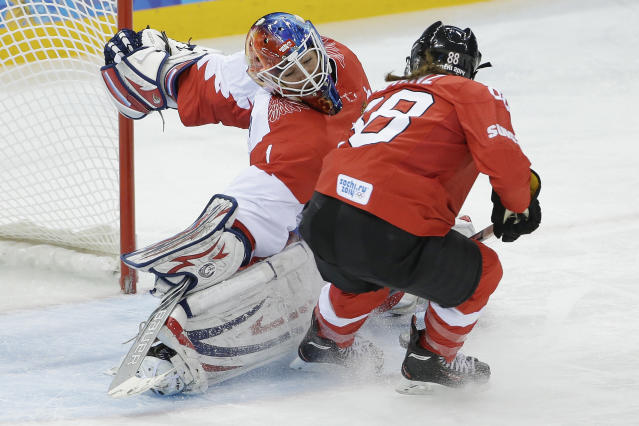 Goalkeeper Anna Prugova of Russia blocks a shot at the goal by Phoebe Stanz of Switzerland during the 2014 Winter Olympics women's ice hockey quarterfinal game at Shayba Arena, Saturday, Feb. 15, 2014, in Sochi, Russia. (AP Photo/Matt Slocum)