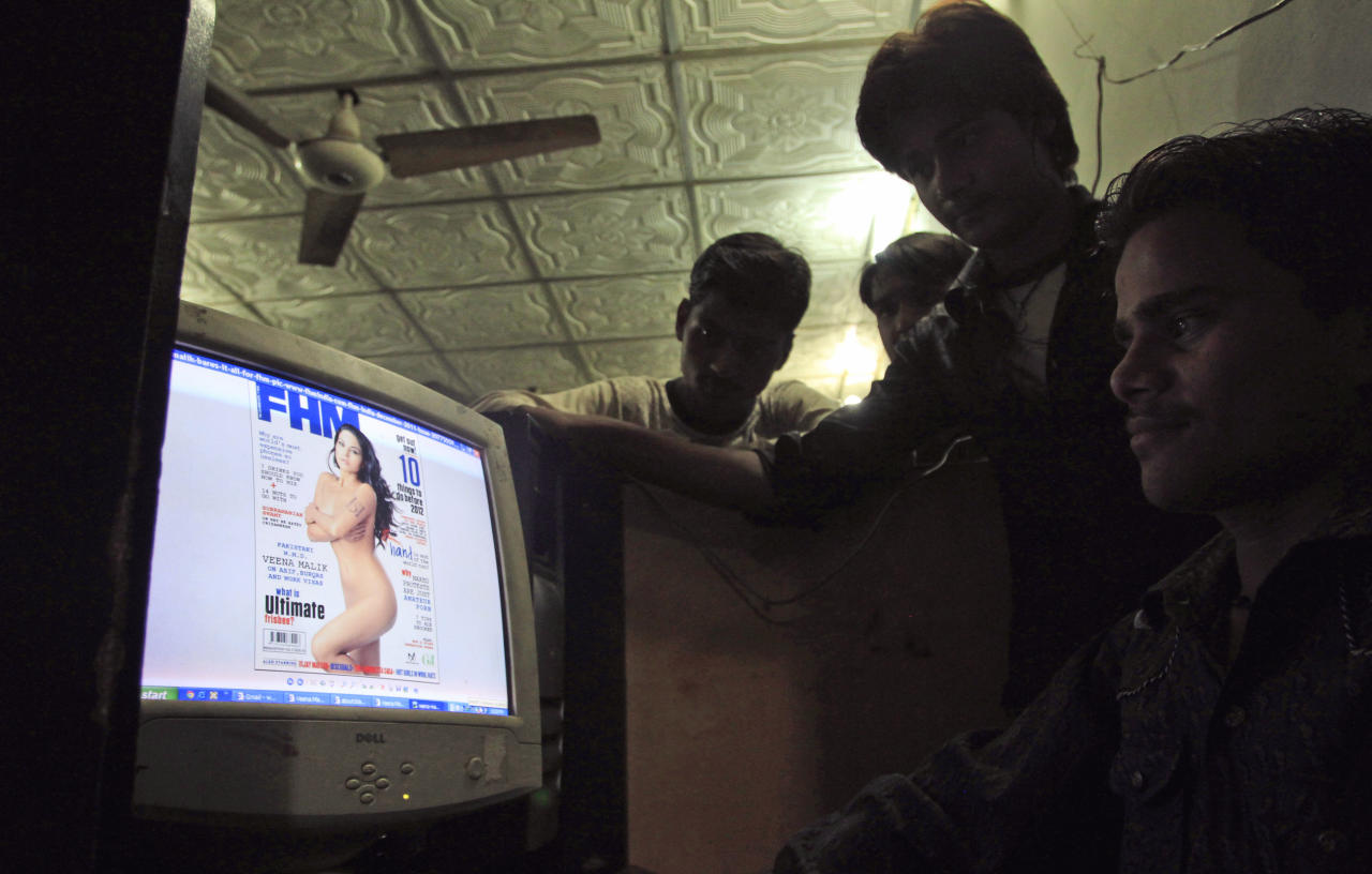 EDS NOTE: PARTIAL NUDITY - Pakistanis look at a website displaying Veena Malik's photo on the website of FHM India, at an Internet cafe in Karachi, Pakistan, Saturday, Dec. 3, 2011. Malik, a Pakistani actress who posed in the nude for the magazine with the initials of Pakistan's feared and powerful intelligence agency on her arm, has triggered fury across Pakistan. Malik's photo on the FHM India website, in advance of its publication in the magazine's December issue, has been lighting up social network sites since earlier this week. (AP Photo/Shakil Adil)
