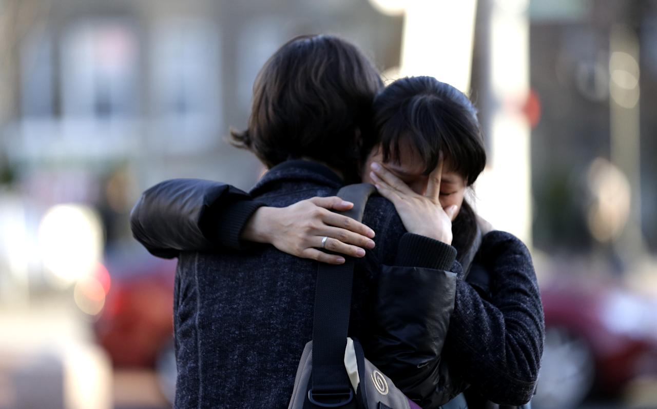 Two theology students embrace following a vigil for Boston University student Lingzi Lu, who was killed in the Boston Marathon explosions, outside the school's Marsh Chapel, Wednesday, April 17, 2013, in Boston. The city continues to cope following Monday's explosions near the finish line of the marathon, which claimed three lives. (AP Photo/Julio Cortez)