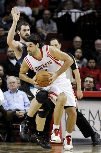 Houston Rockets' Luis Scola, right, posts up on Minnesota Timberwolves' Kevin Love, left, in the first half of an NBA basketball game, Monday, Jan. 30, 2012, in Houston. (AP Photo/Pat Sullivan)