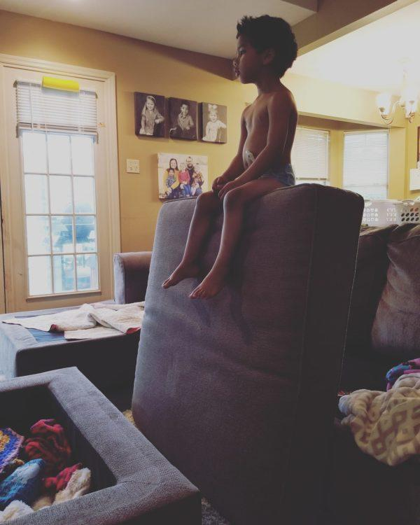 little boy sitting on top of couch cushion