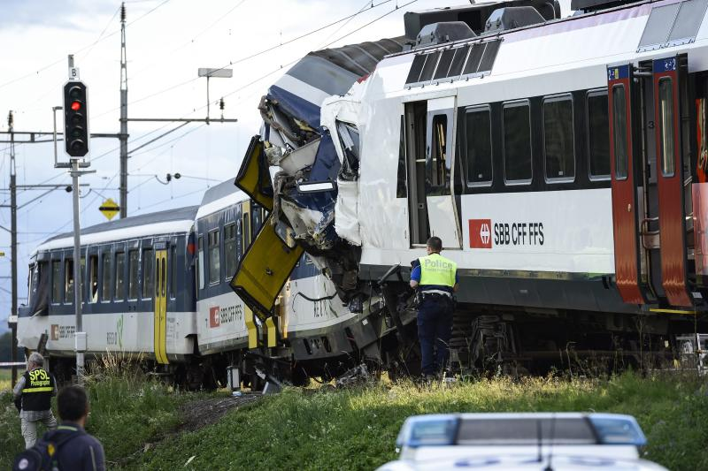 Police inspect the site where two passenger trains collided head-on in Granges-pres-Marnand, western Switzerland, Monday, July 29, 2013. Numerous people have been injured. (AP Photo/Keystone, Laurent Gillieron)