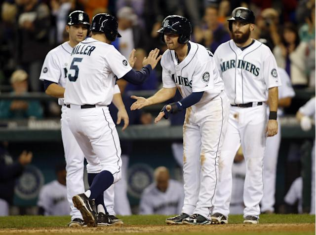 Seattle Mariners' Brad Miller (5) is greeted at home by Mike Zunino, left, Nick Franklin, second from right, and Dustin Ackley right, after hitting a grand slam on a pitch from Oakland Athletics' Jarrod Parker during the fifth inning of a baseball game in Seattle, Saturday, Sept. 28, 2013. (AP Photo/John Froschauer)