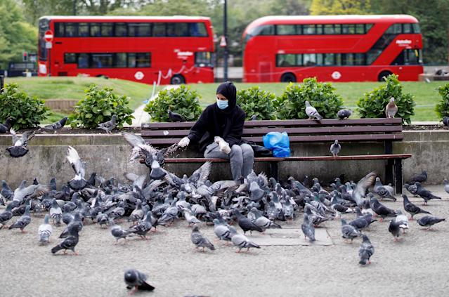 A woman wearing a facemask feeds birds in London during the lockdown. (Getty)