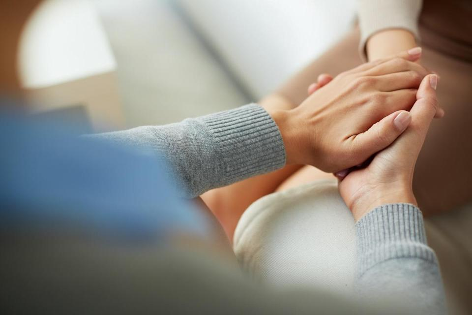 Close-up of psychiatrist hands together holding palm of her patient