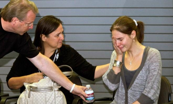 Amanda Knox is comforted by her mother and father before speaking to the media in Seattle on Oct. 4, 2011.