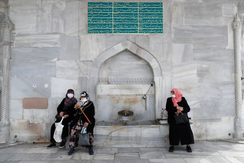 Women wearing protective face masks sit at an old fountain in Istanbul