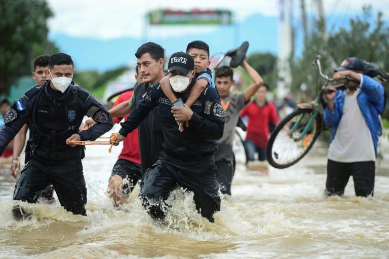 Honduran police in El Progreso help evacuate flood victims after a river overflowed due to heavy rain from storm Eta